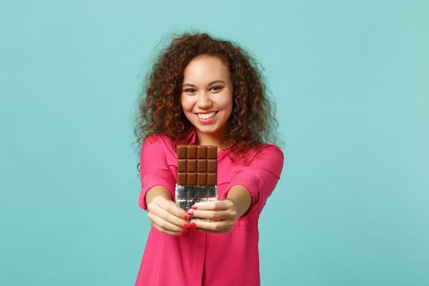 Il ritratto della ragazza africana sveglia sorridente in vestiti casuali tiene in mano la barretta di cioccolato isolata sul fondo della parete turchese blu in studio. persone sincere emozioni, concetto di stile di vita. mock up copia spazio.