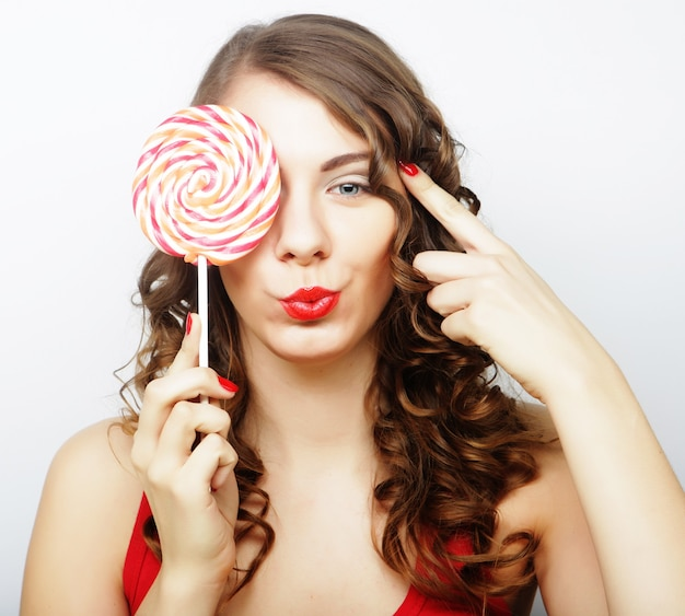 Ritratto di una ragazza carina sorridente che si copre gli occhi con lecca-lecca su sfondo bianco