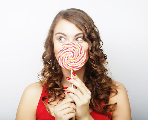 Ritratto di una ragazza carina sorridente che si copre le labbra con lecca-lecca su sfondo grigio