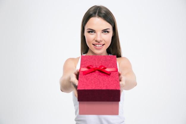 Ritratto di una ragazza carina sorridente che dà una confezione regalo alla telecamera isolata