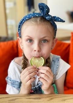 Ritratto di bambina carina sorridente che tiene le fette di lime