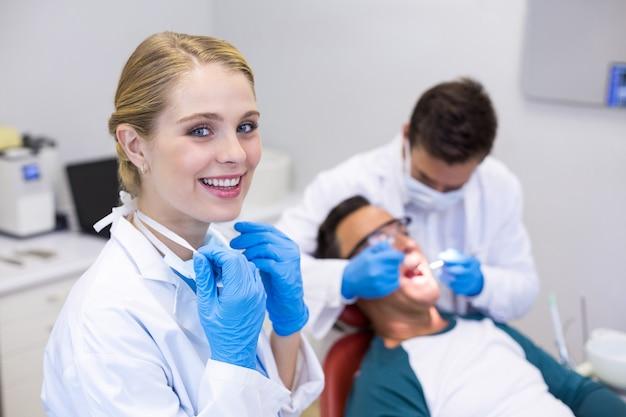 Ritratto del dentista sorridente in piedi mentre il suo collega esamina il paziente
