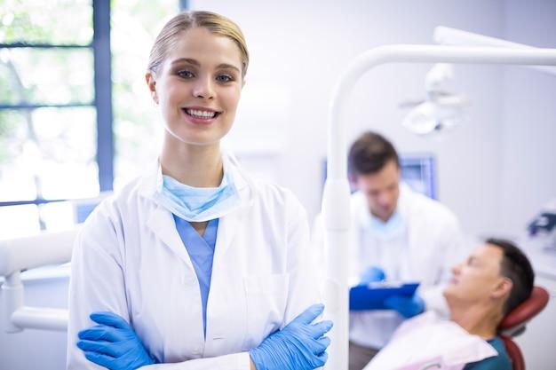 Ritratto di dentista sorridente in piedi con le braccia incrociate