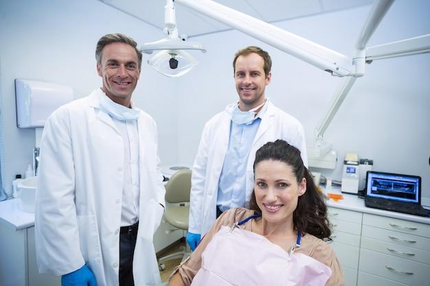 Ritratto di dentisti sorridenti e paziente femminile