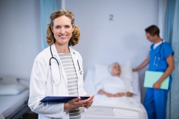 Ritratto di medico sorridente che sta con la lavagna per appunti