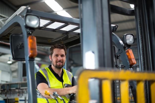 Ritratto dell'operaio sorridente che guida carrello elevatore