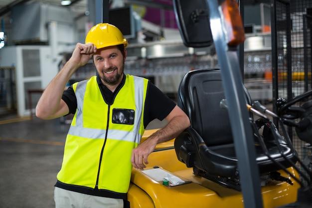 Ritratto dell'operaio sorridente che si appoggia carrello elevatore