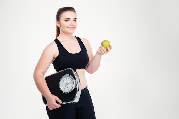 Ritratto di una donna grassa sorridente che tiene in mano una bilancia e una mela isolate su un muro bianco