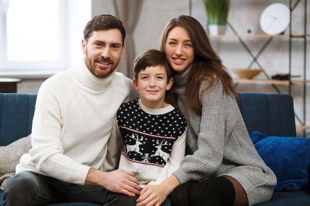 Ritratto di padre sorridente, madre e figlio, famiglia felice che trascorrono del tempo insieme a casa, ragazzo carino con...