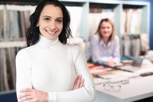 Ritratto del consulente femminile sorridente nel salone del tessuto. concetto di regole del servizio clienti