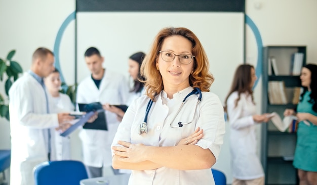 Ritratto di sorridere donna medico soddisfatto del suo lavoro in un ospedale sanitario. professionisti medici al lavoro. pediatra medico femminile in camice bianco con lo stetoscopio sul collo.