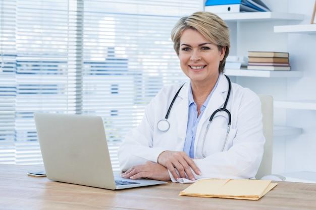 Ritratto di medico femmina sorridente seduto alla scrivania con il computer portatile