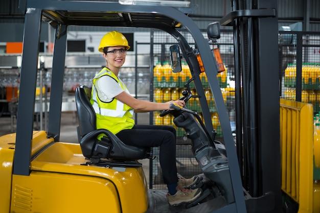 Ritratto dell'operaio femminile sorridente che guida carrello elevatore