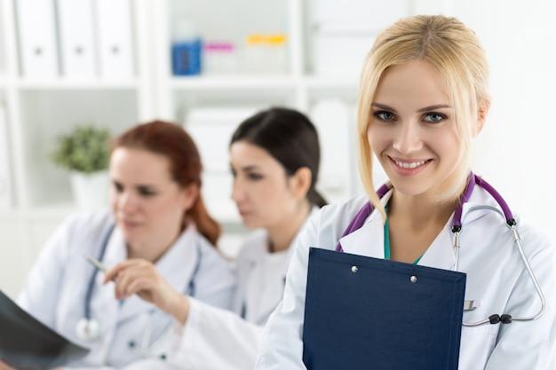 Ritratto del medico femminile sorridente della medicina che tiene la cartella blu del documento con due colleghi che esaminano l'immagine dei raggi x. concetto di sanità e medicina.