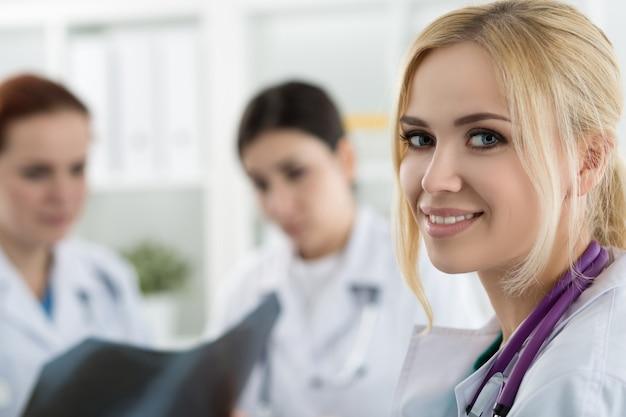Ritratto del medico femminile sorridente della medicina con due colleghi che esaminano l'immagine dei raggi x. concetto di sanità e medicina.