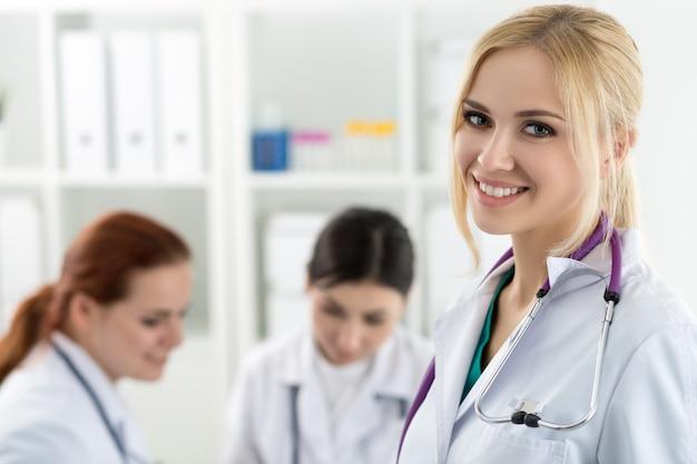 Ritratto del medico di medicina femminile sorridente con due colleghi che lavorano. concetto di sanità e medicina.