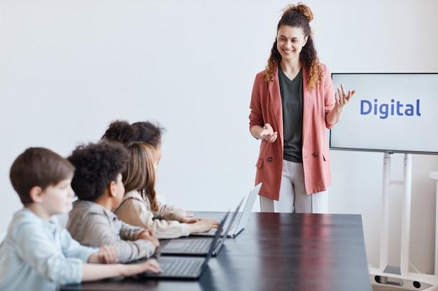 Ritratto di un'insegnante femminile sorridente che parla con un gruppo di bambini che usano i computer durante la lezione di informatica a scuola