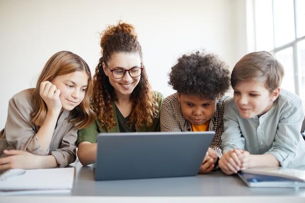 Ritratto di insegnante femminile sorridente che utilizza computer con un gruppo eterogeneo di bambini