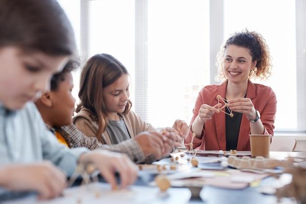 Ritratto di insegnante femminile sorridente con un gruppo di bambini che si godono la lezione di arti e mestieri a scuola, copia spazio