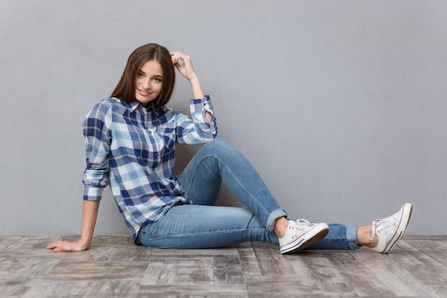Ritratto di un'adolescente sorridente seduta sul pavimento su un muro grigio