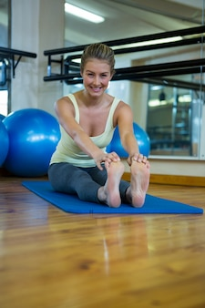 Ritratto di donna in forma sorridente facendo esercizio di stretching sulla stuoia