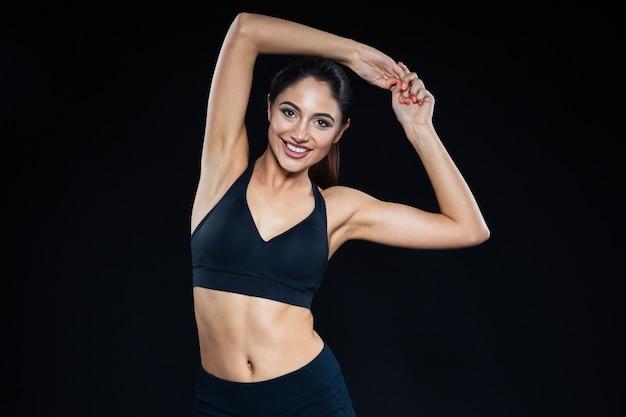 Ritratto di una donna sorridente di fitness in posa su sfondo nero