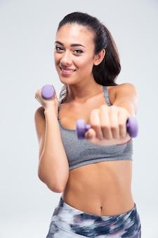 Ritratto di un allenamento di donna fitness sorridente con manubri isolato su un muro bianco