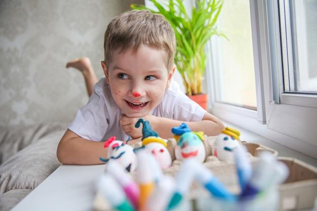 Ritratto di un bambino di quattro anni sorridente con una faccia dipinta sdraiato sul davanzale della finestra davanti alle uova di pasqua decorate.