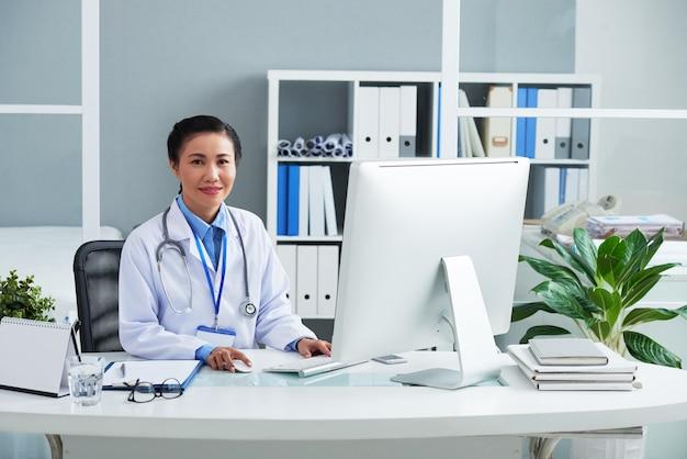 Ritratto di medico generico sorridente in camice che lavora al computer alla sua scrivania in ufficio