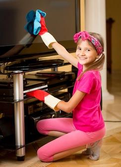 Ritratto di una ragazza sorridente che fa i lavori domestici su un grande schermo tv di pulizia