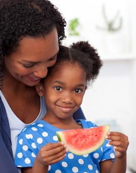 Ritratto di una ragazza sorridente che mangia frutta