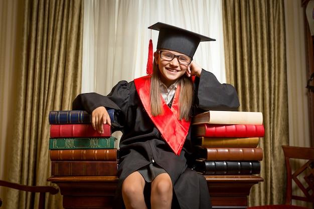Ritratto di ragazza sorridente con berretto da laurea e abito seduto sul tavolo e appoggiato sui libri