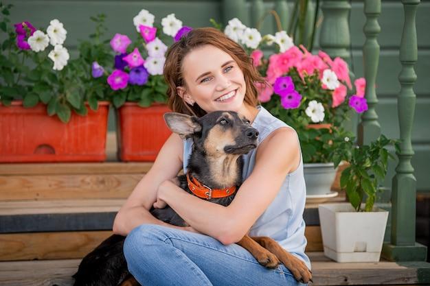 Ritratto di una ragazza sorridente che abbraccia un grosso cucciolo divertente