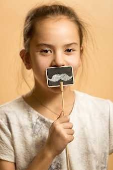 Ritratto di ragazza sorridente in posa con baffi artificiali sul bastone