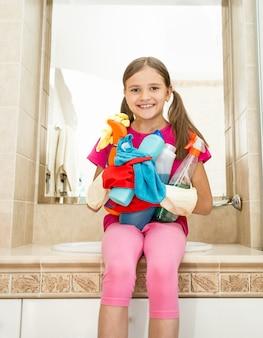 Ritratto di ragazza sorridente in posa con bottiglie di detergente e stracci in posa in bagno