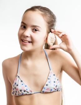 Ritratto di ragazza sorridente in posa con conchiglia accanto all'orecchio