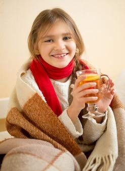 Ritratto di ragazza sorridente in sciarpa ricoperta di plaid che tiene tazza di tè caldo