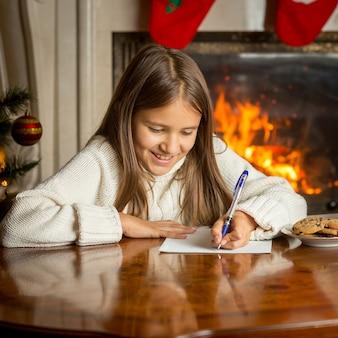 Ritratto di una ragazza sorridente con un maglione seduta accanto al caminetto e che scrive una lettera a babbo natale