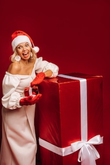 Ritratto di una ragazza sorridente in abito bianco e cappello da babbo natale con un regalo di natale su sfondo rosso.