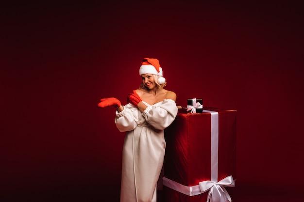 Ritratto di una ragazza sorridente in abito bianco e cappello da babbo natale con un enorme regalo di natale su sfondo rosso.