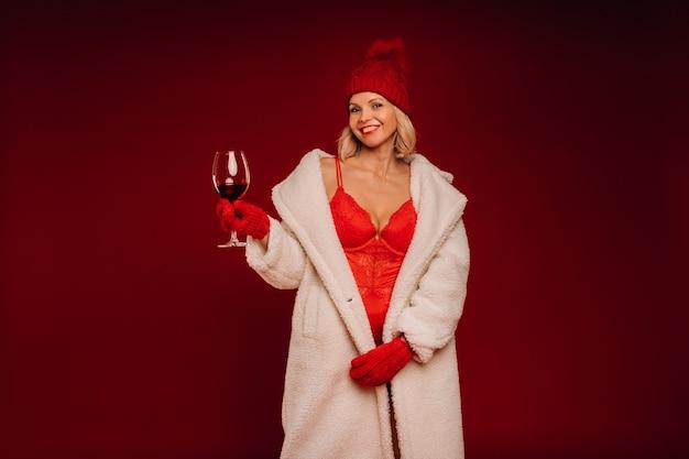 Ritratto di una ragazza sorridente in una pelliccia bianca e biancheria intima che tiene un bicchiere di champagne su uno sfondo rosso.
