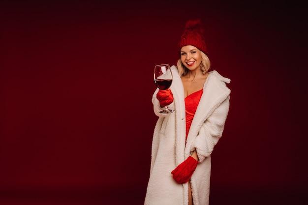 Ritratto di una ragazza sorridente in un cappotto di pelliccia bianca e biancheria intima con in mano un bicchiere di champagne su uno sfondo rosso.