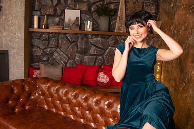 Ritratto di ragazza sorridente che si siede sul divano in abito. abito in colore alla moda tidewater green. sullo sfondo presenta