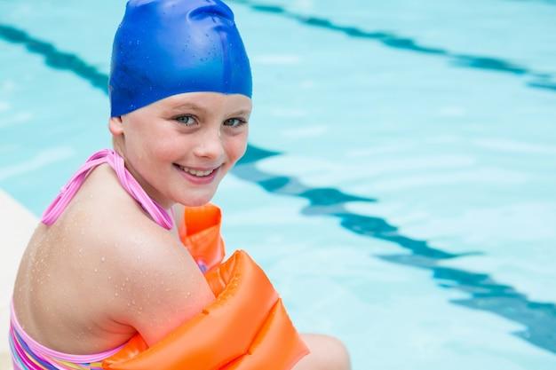 Ritratto di ragazza sorridente con cuffia da bagno seduto vicino a bordo piscina