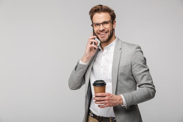 Ritratto di un bell'uomo sorridente con gli occhiali che parla al cellulare e tiene in mano un bicchiere di carta isolato su un muro bianco