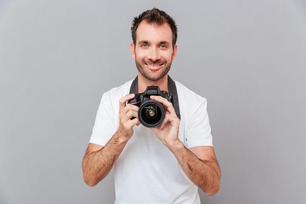 Ritratto di un bell'uomo sorridente che tiene la macchina fotografica isolata su uno sfondo grigio