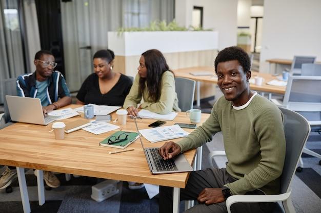 Ritratto di un bel giovane nero sorridente che partecipa a una riunione d'affari e lavora al computer portatile