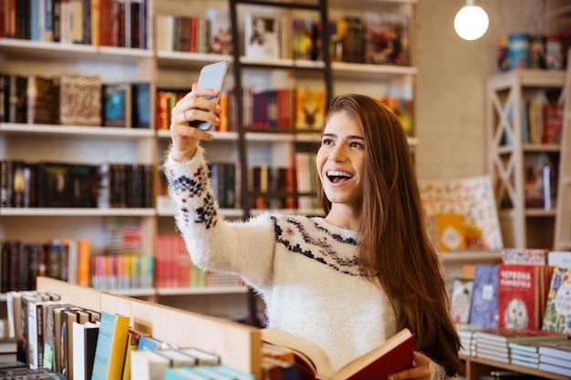 Ritratto di una ragazza sorridente felice che si fa selfie mentre è seduta in biblioteca