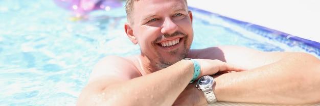 Ritratto di uomo felice sorridente in piscina all'aperto
