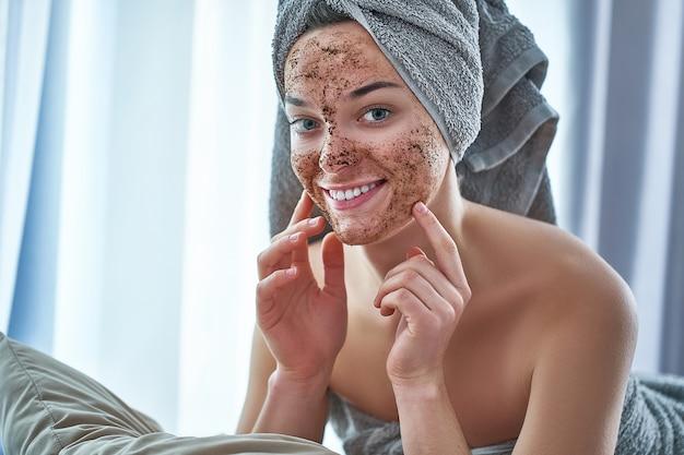 Il ritratto della donna felice sorridente in asciugamano di bagno con il caffè del fronte naturale sfrega la maschera dopo la doccia